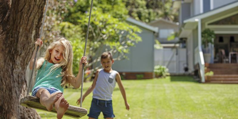 Son pushing daughter on a swing in the front yard.