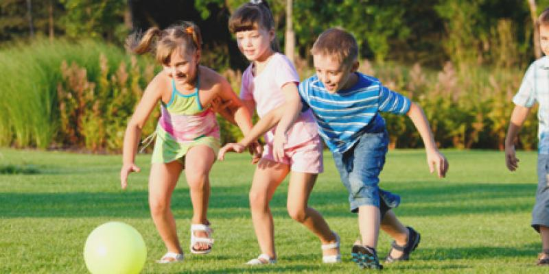 Four children playing with a soccer ball in the lawn.
