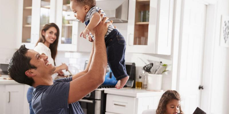 father holding up his baby while they stand in their ant free kitchen while the mother looks at them.