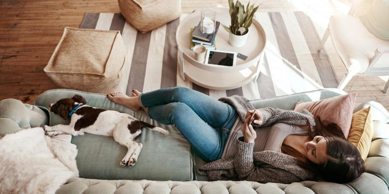 woman sitting in living room on her couch with her small dog enjoying a flea free home thanks to Got Bug's outdoor flea control.