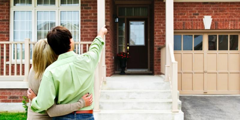 Couple pointing at their home that is pest and termite free.